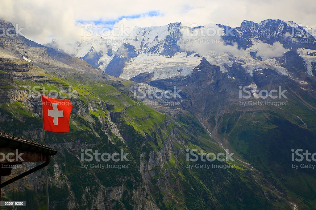 Swiss Flag winding above Lauterbrunnen valley alpine massif, Swiss Alps stock photo