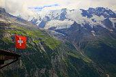 Swiss Flag winding above Lauterbrunnen valley alpine massif, Swiss Alps