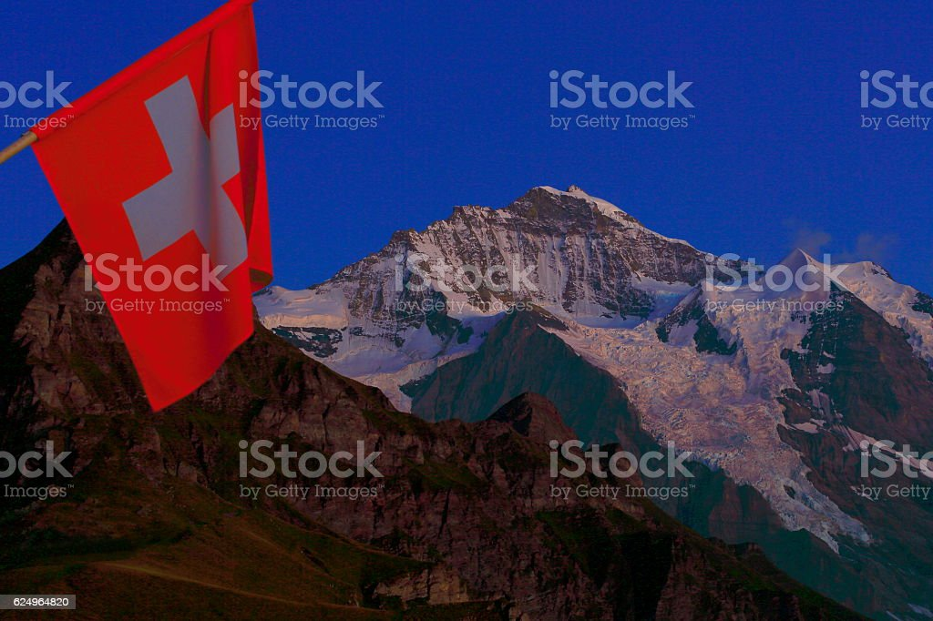 Swiss flag winding in front of Jungrau at evening, Swiss Alps stock photo