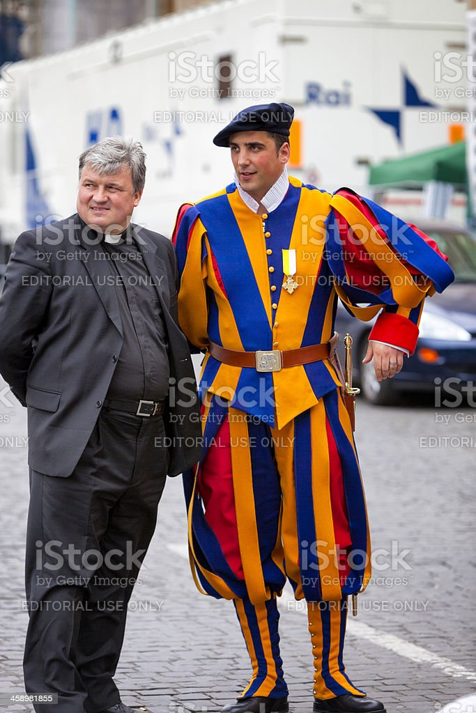 Swiss guard on dutty and a Priest at Vatican City stock photo
