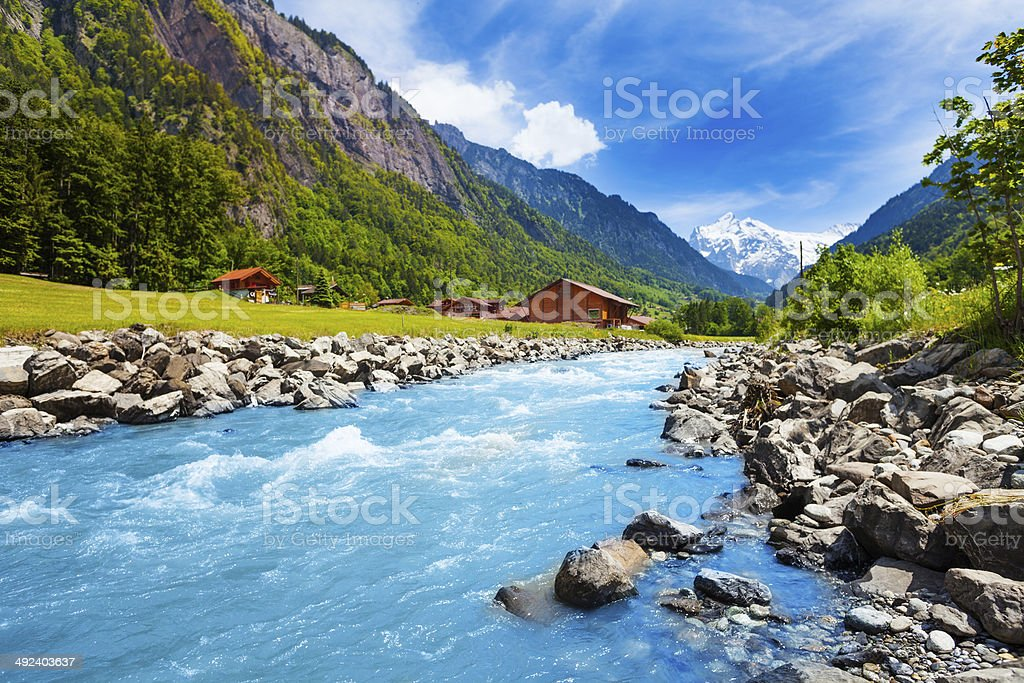 Swiss landscape with river stream and houses stock photo