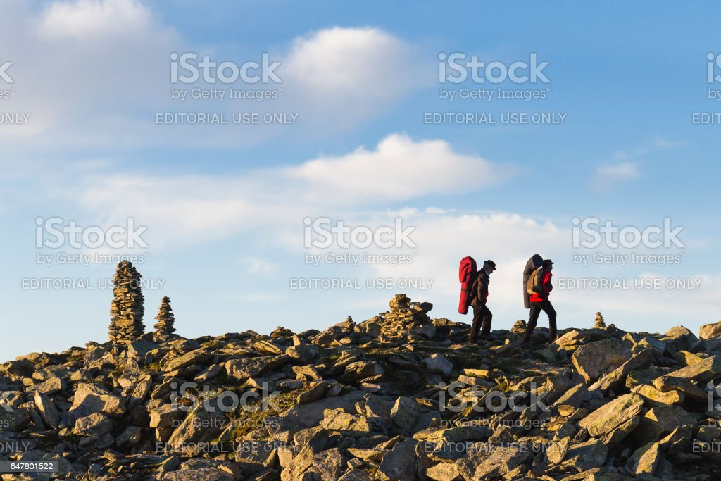 Swiss musicians, on the top of mountain, carrying backpack which contained traditional horns. stock photo