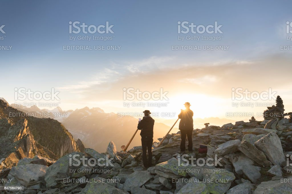 Swiss musicians playing  traditional horn on top of Mount Eggishorn during sunrise. stock photo