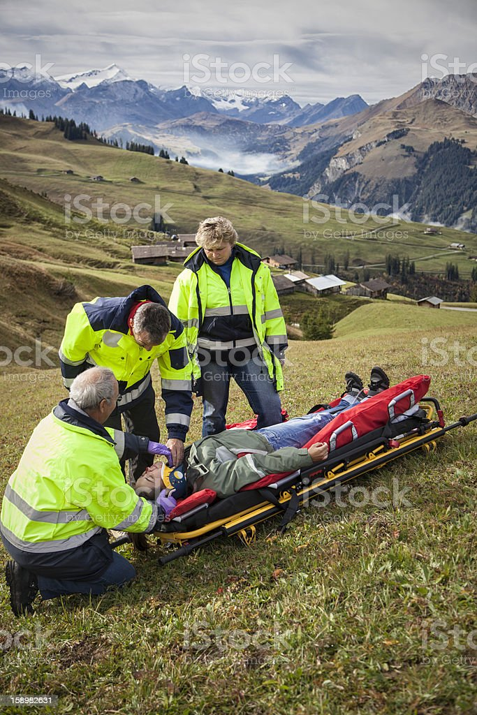 Swiss Paramedics Team Care For Injured Woman in Alps stock photo