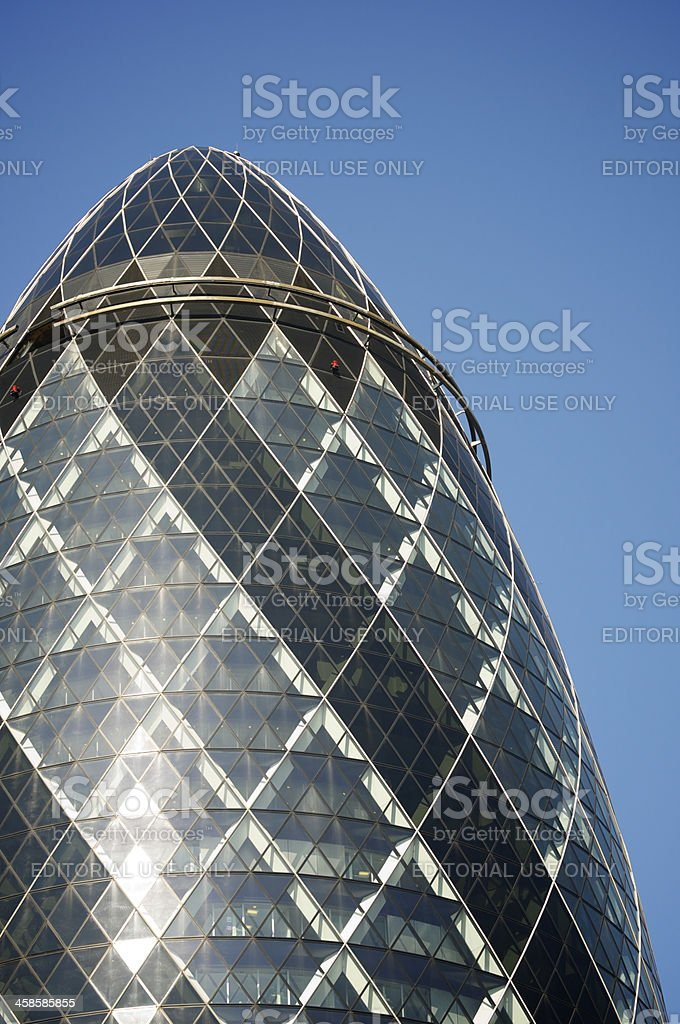 Swiss Re Gherkin Building Shines Against Blue Sky London stock photo