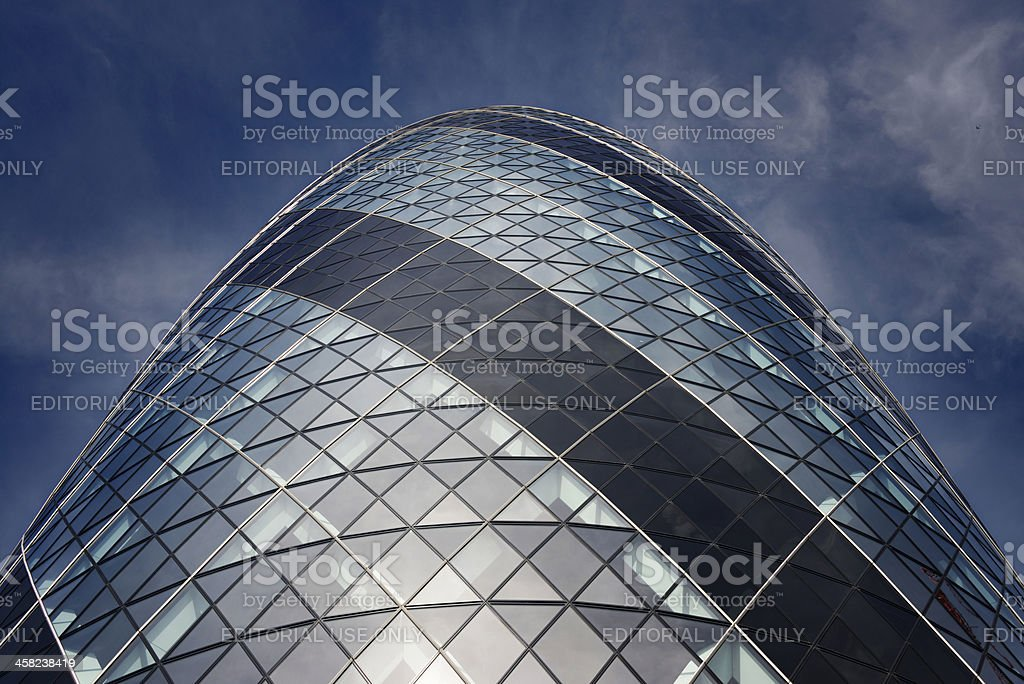 Swiss Re Tower shines against a cloudy sky in London royalty-free stock photo