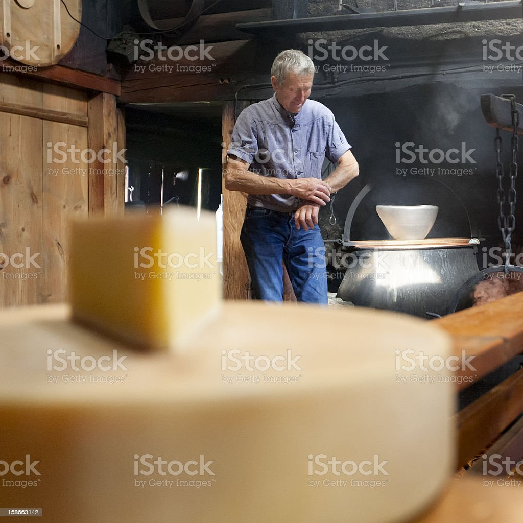 Swiss Traditional Cheesemaker Looking at Wrist Watch. stock photo
