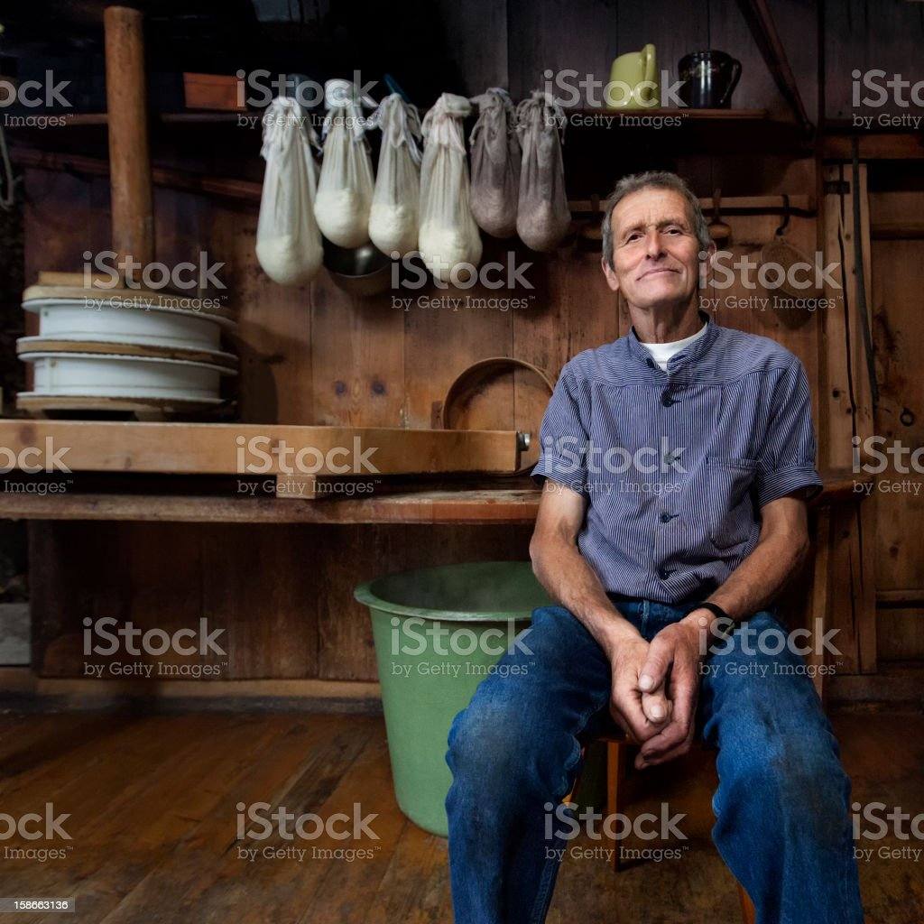 Swiss Traditional Cheesemaker Smiling In Wooden Farmhaus. stock photo