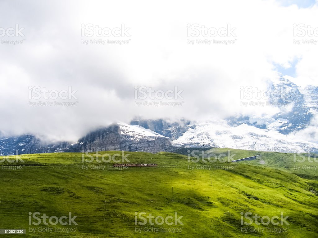 Swiss train during summer with alpine landscape in mountains in Interlaken with cloudy foggy mist stock photo