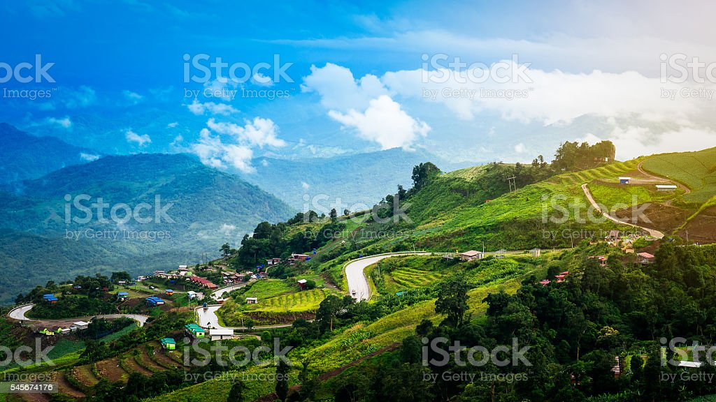 Switchback and village on mountain with blue sky landscape stock photo