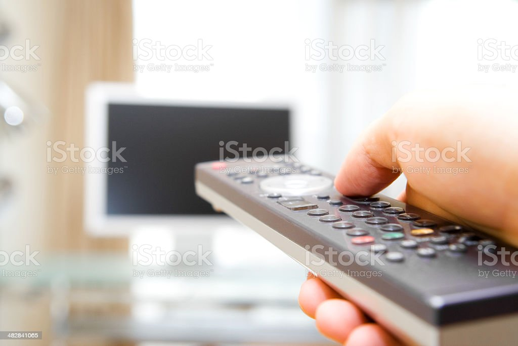 Switching TV channels with the remote control stock photo