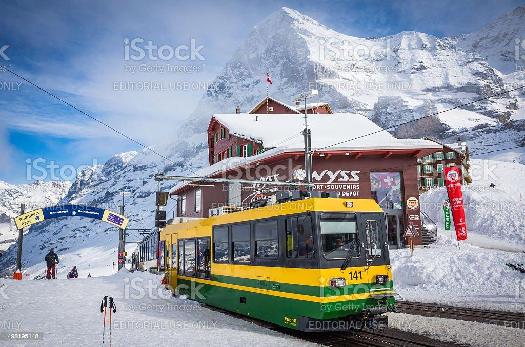 Switzerland skiers and mountain railway train beneath Eiger winter Alps stock photo