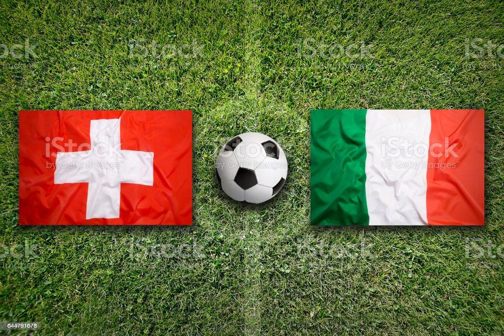 Switzerland vs. Italy flags on soccer field stock photo
