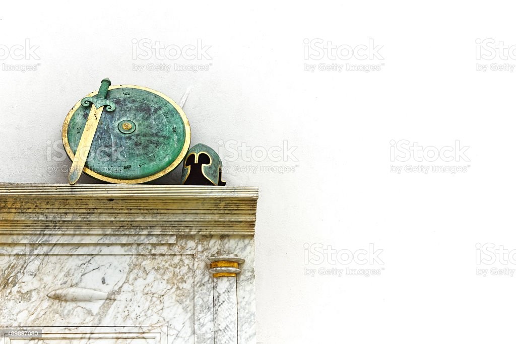 Sword, shield and helmet resting on marble base, war concept stock photo