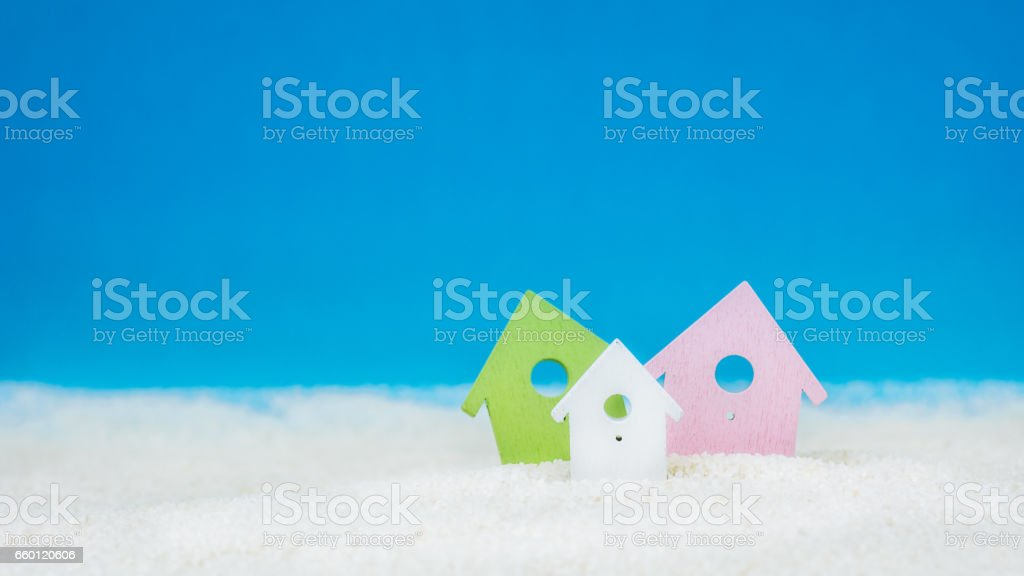 Symbol of tree coloured little houses on the sand on bright blue background stock photo