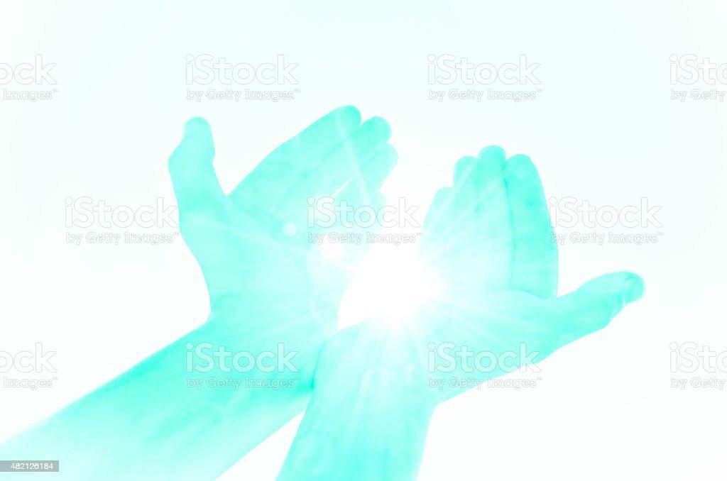 Symbolic hands providing light stock photo