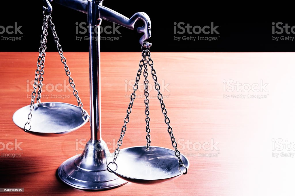 Symbolic Scales of Justice brightly lit on wooden desk stock photo