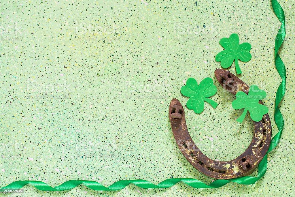 Symbols of St. Patrick's Day: old horseshoe, shamrock clover, gr stock photo