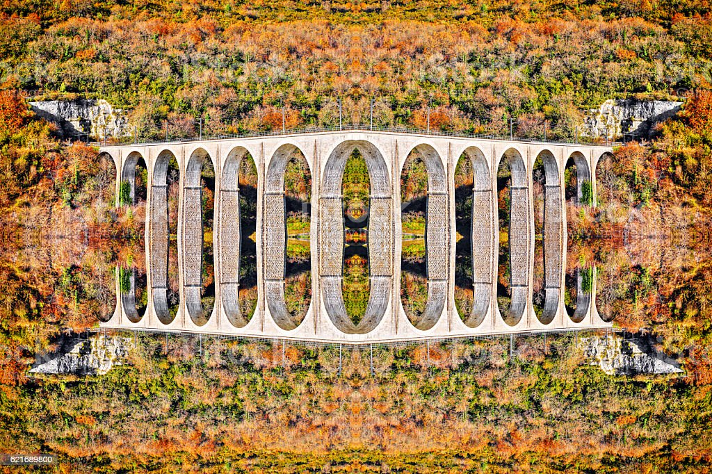 Symmetric surreal kaleidoscope shape of french old stone viaduct bridge stock photo