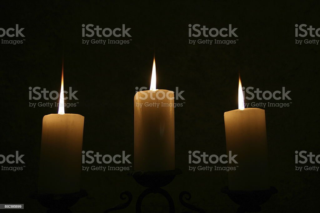 Symmetrical composition of three candles stock photo