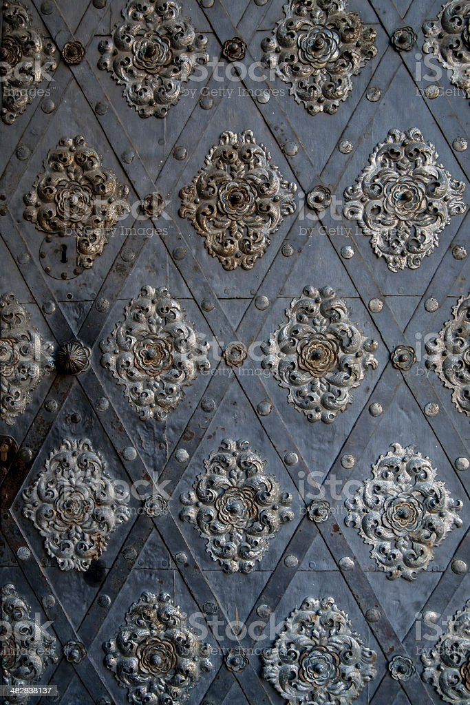 Symmetrical floral pattern on the metal door. stock photo