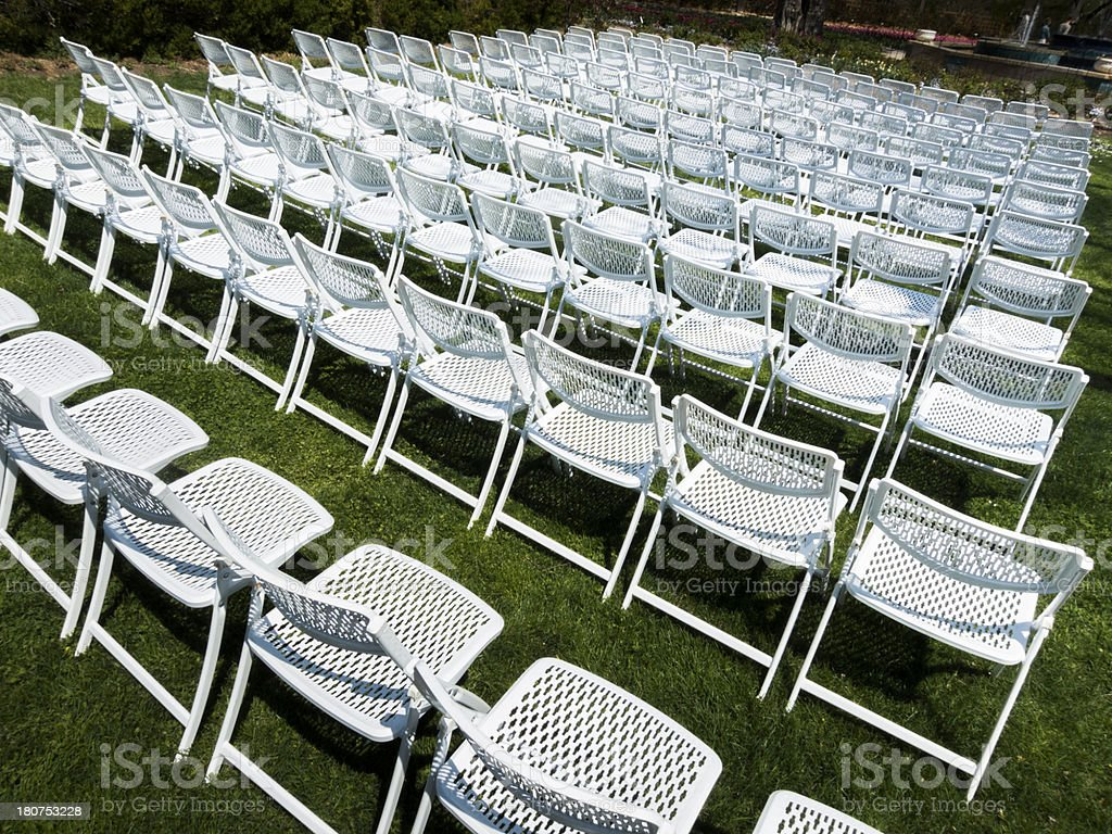 Symmetrical Pattern Of White Folding Chairs At Outdoor Garden Event royalty-free stock photo