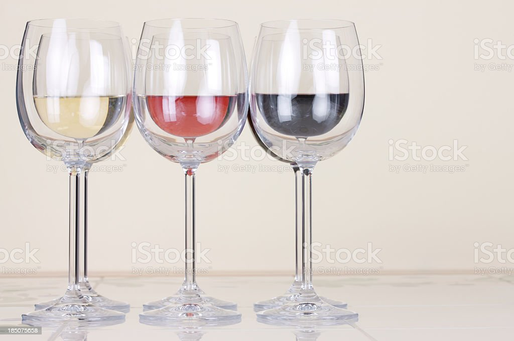Symmetrically placed glasses of white,red and Rose wine royalty-free stock photo