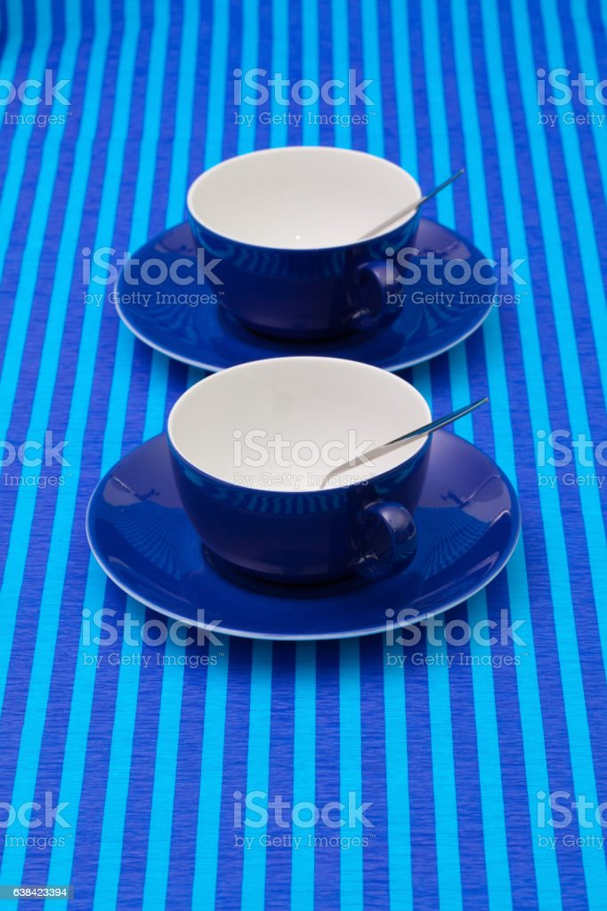 Symmetry  arrangement empty cups of tea on blue striped tableclo stock photo