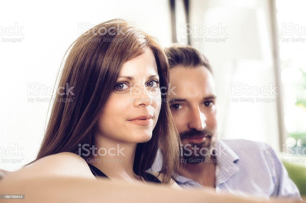 sympathic beautiful young couple relaxing on couch looking to camera stock photo