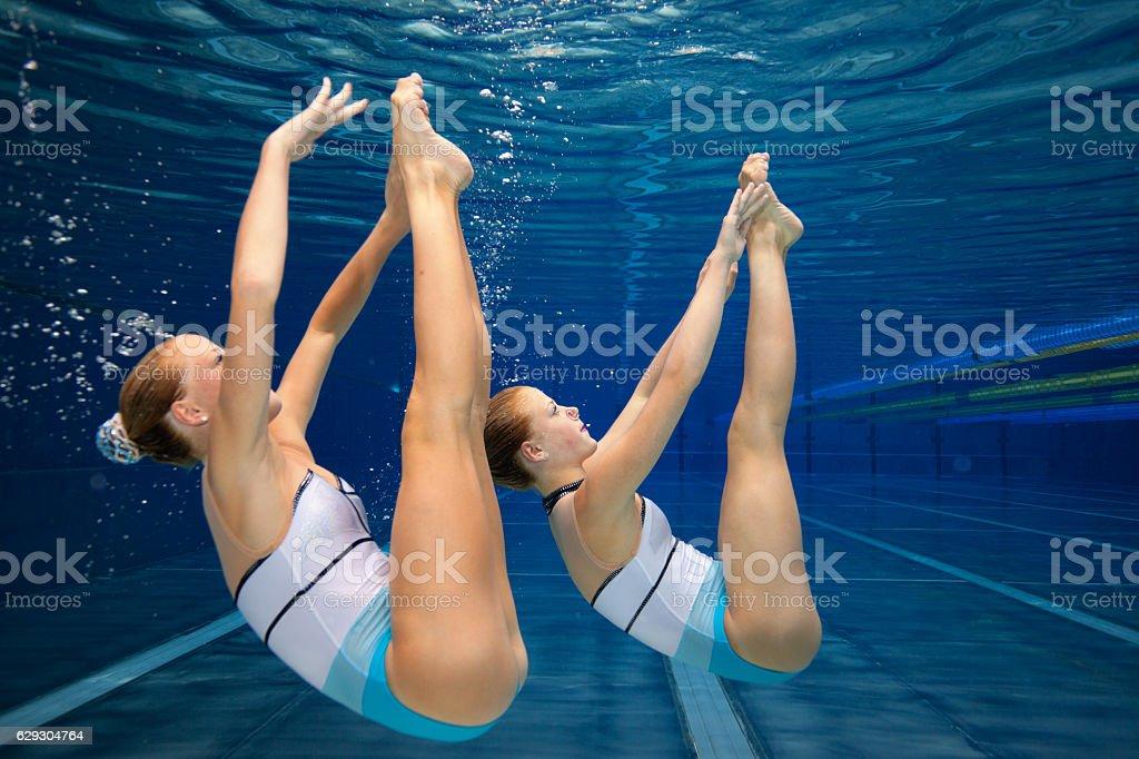 synchronised swimming underwater exercise stock photo