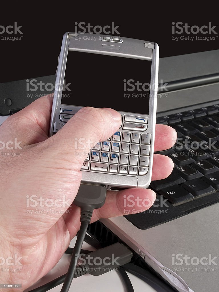 synchronization of data between personal digital assistent and laptop stock photo