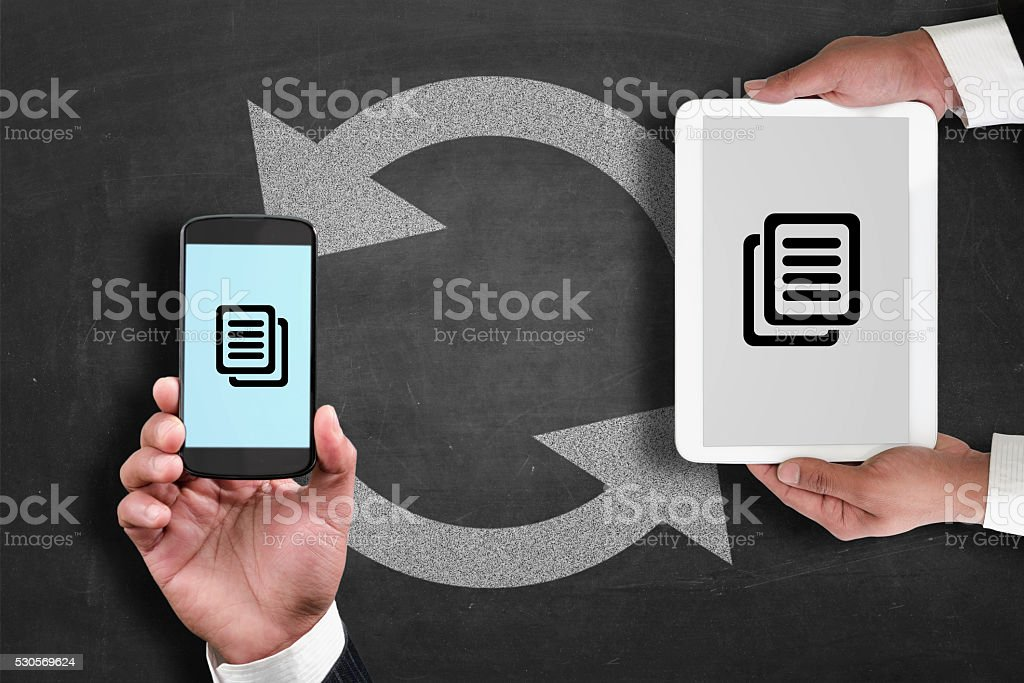 Synchronizing data from digital tablet to smartphone stock photo