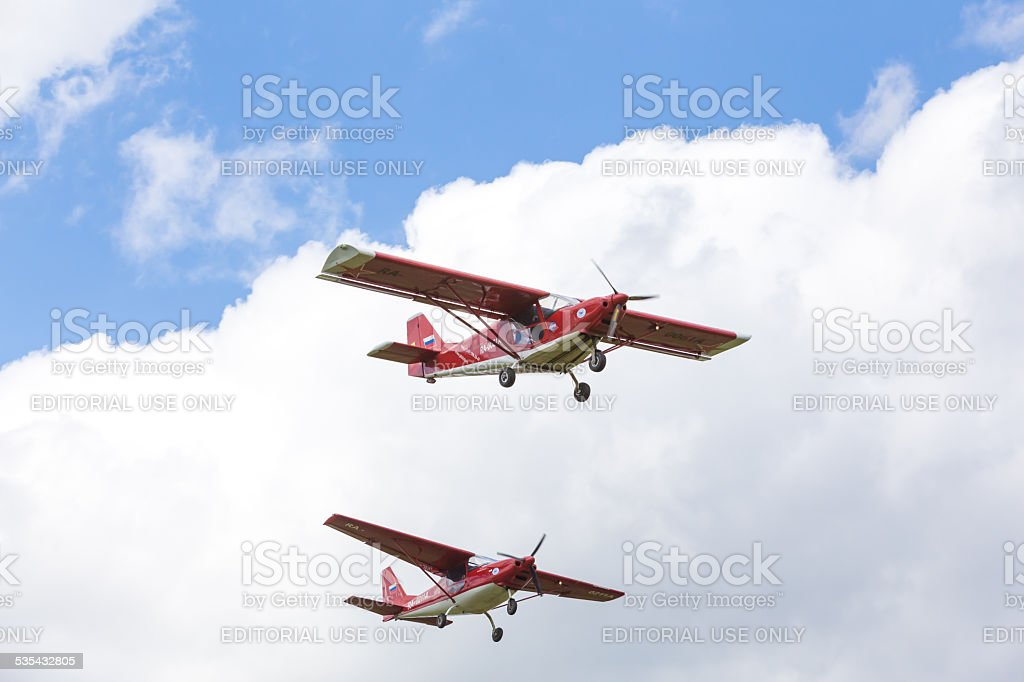 Synchronous flight of two red airplanes closeup at  Festival stock photo