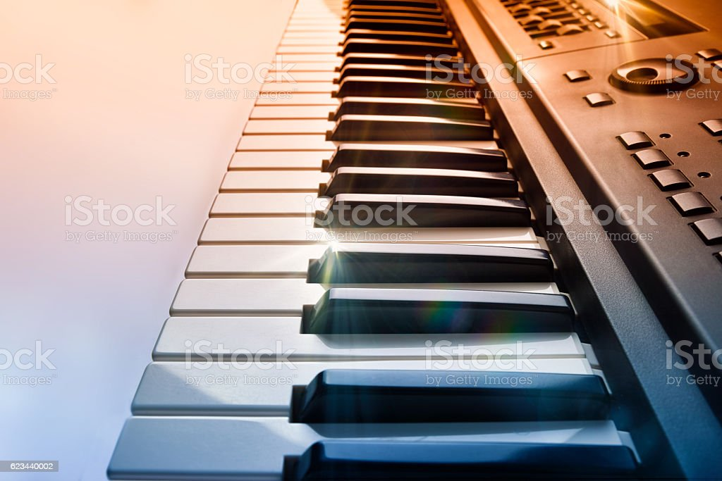 Synthesizer keyboard with shine and blue red gradient side view stock photo