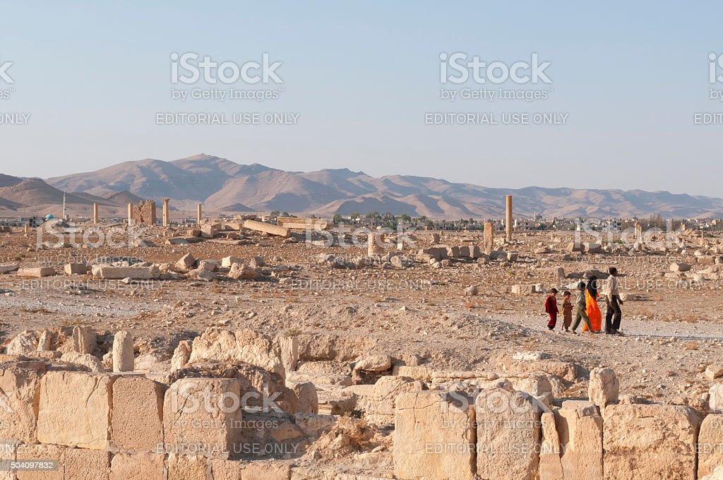 Syrian family walking in Palmyra ruins stock photo