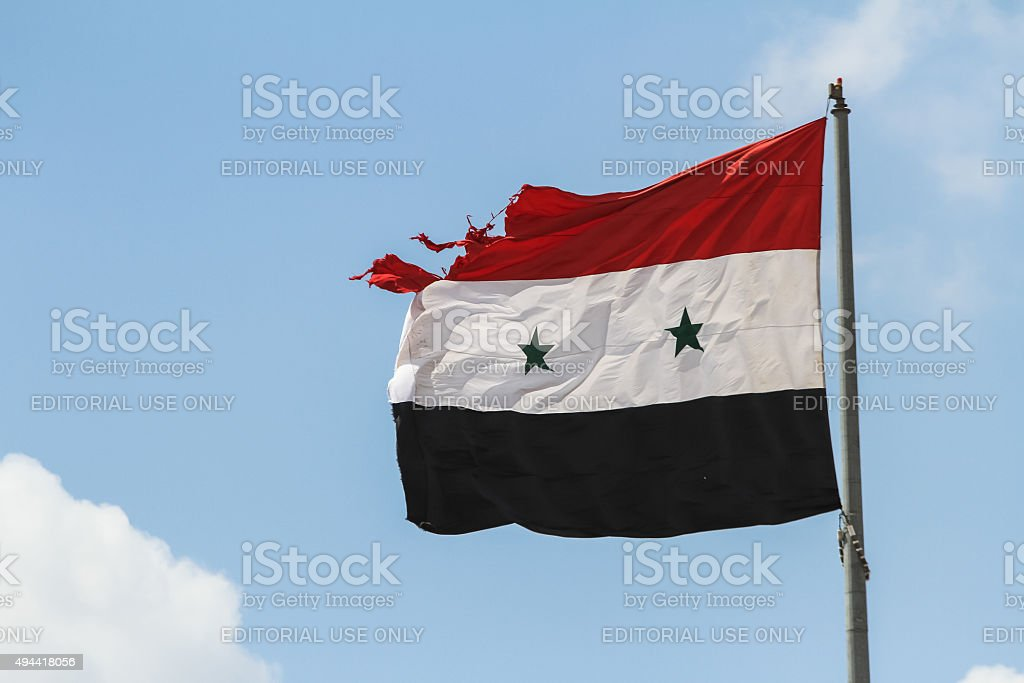 Syrian flag is damaged by gunfire stock photo