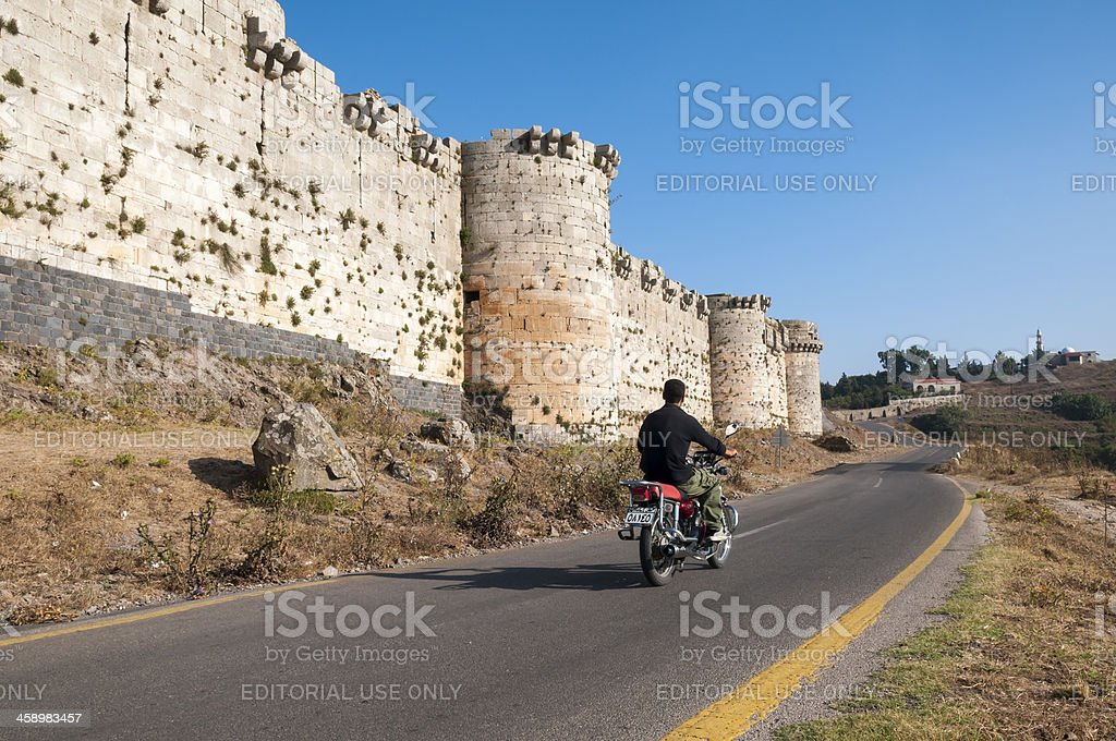 Syrian man on motorcycle at Crac des Chevaliers, Syria royalty-free stock photo