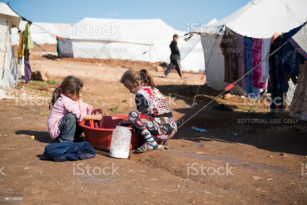 Syrian refugee children washing clothes stock photo