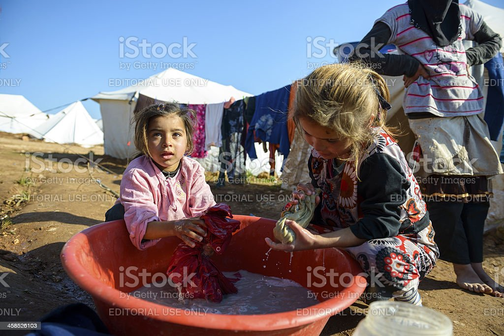 Syrian refugee kids washing clothes in Atmeh, Syria stock photo