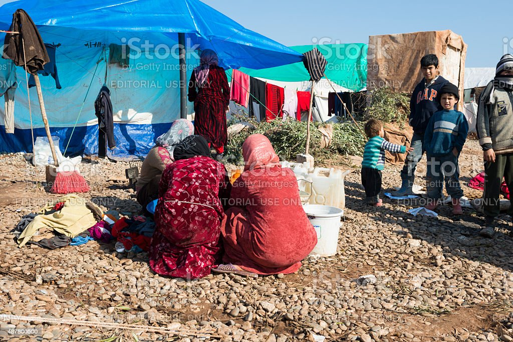Syrian refugee women washing clothes in refugee camp stock photo