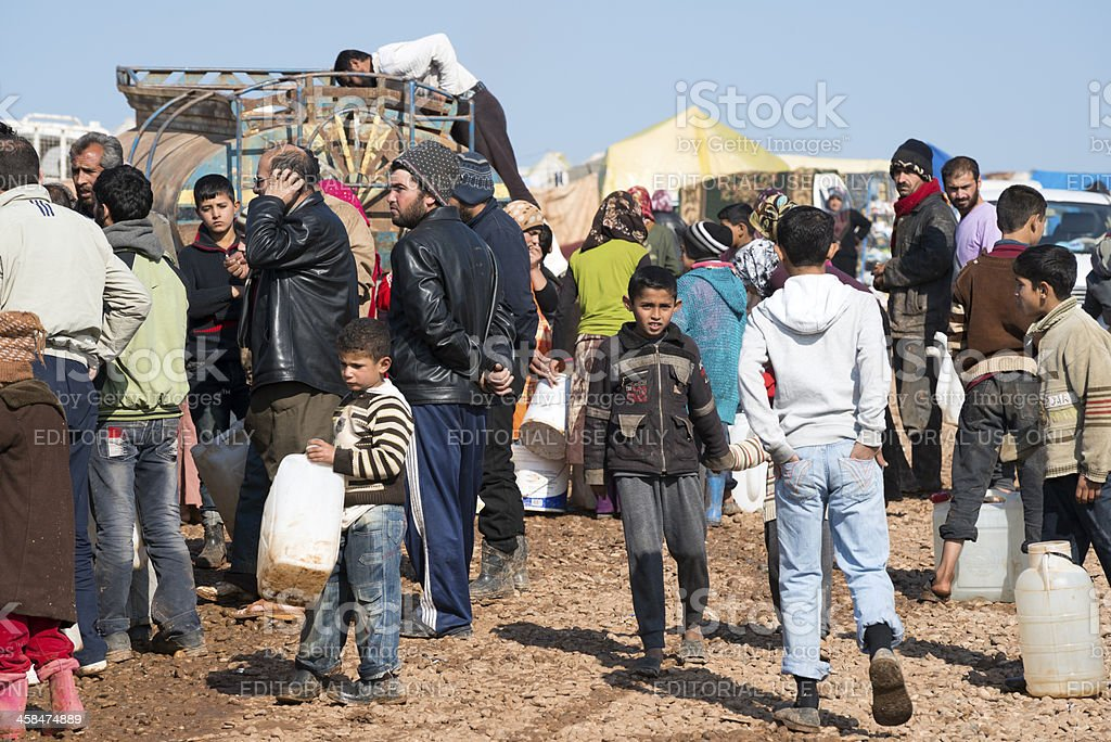Syrian refugees waiting for water at IDP camp stock photo