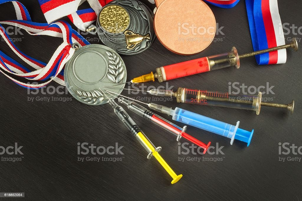 Syringe and medals. Doping in sport. Doping athletes. stock photo
