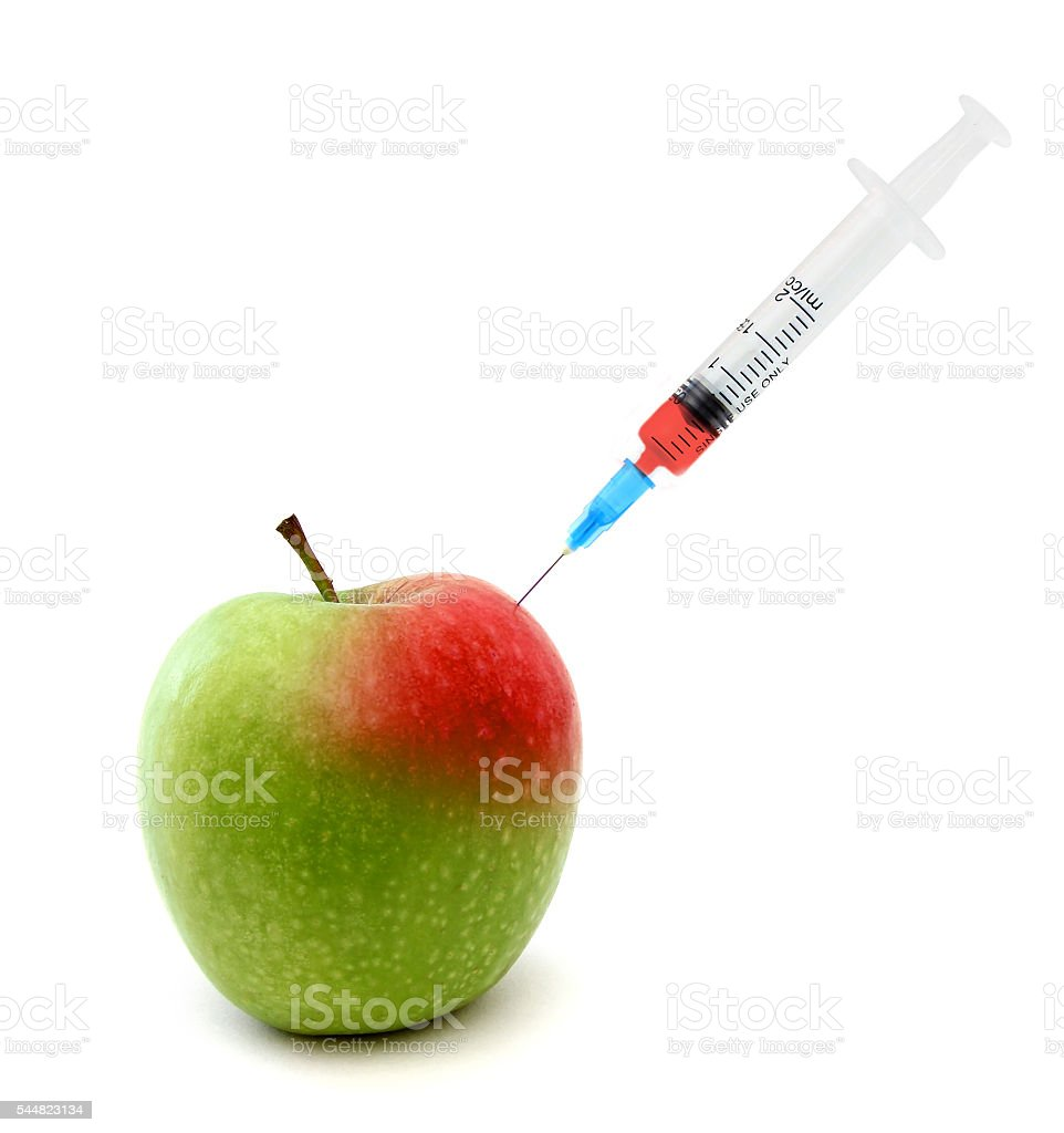 Syringe in an apple stock photo