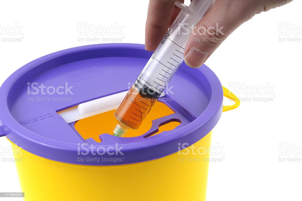 Syringe into a Sharpsbin royalty-free stock photo