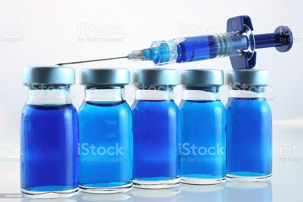 Syringe on bottles stock photo