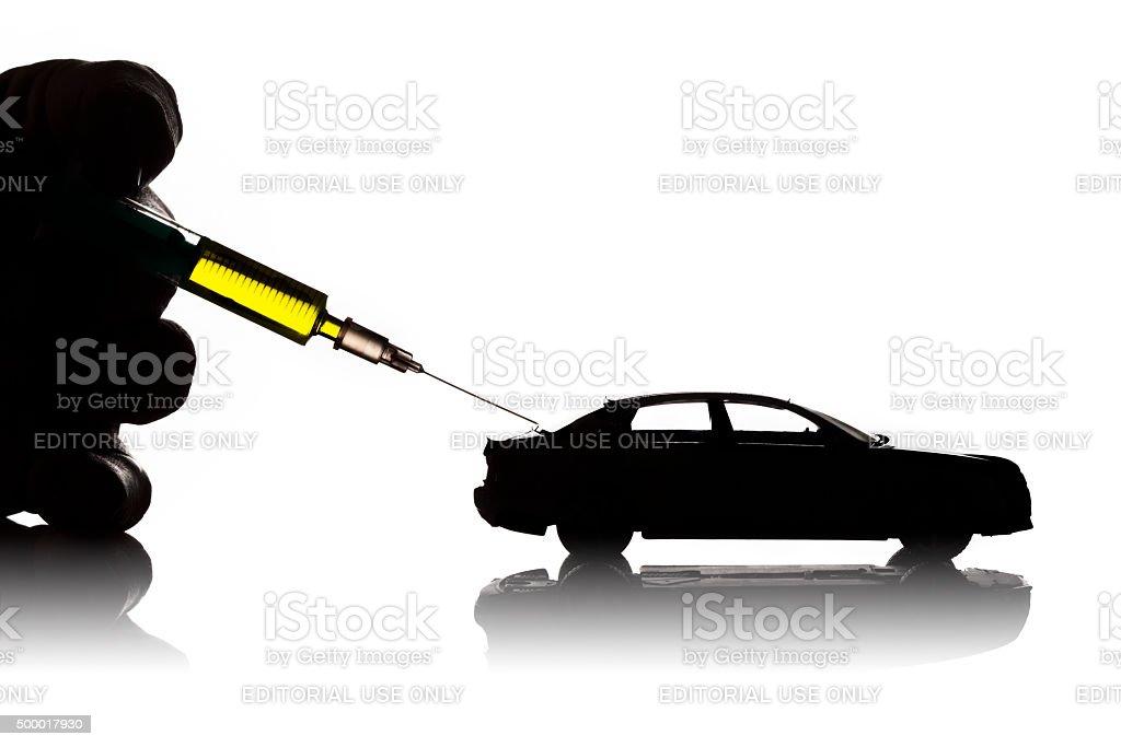 Syringe on toy car, backlit silhouette tuning stock photo