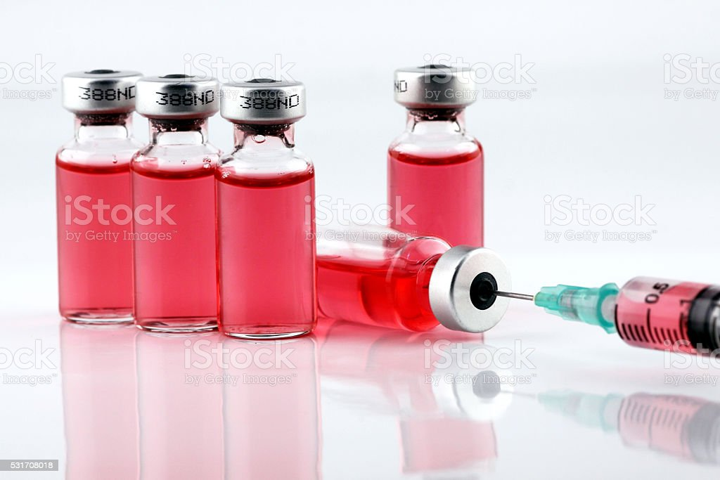 syringe sucks the vaccine from a bottle stock photo