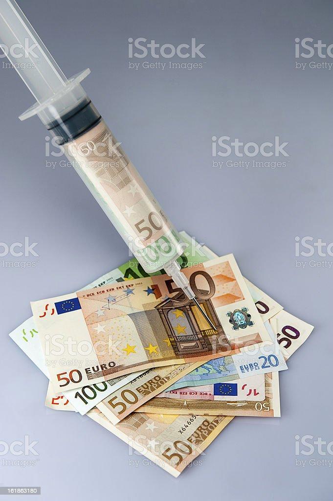Syringe with money injecting cash stock photo