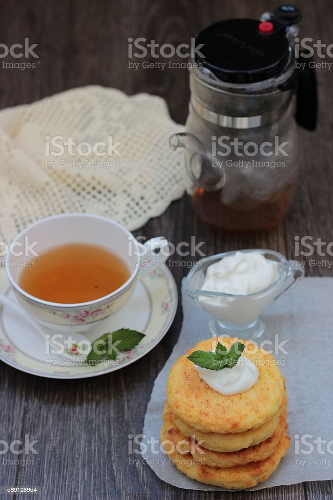 Syrniki. Russian cottage cheese pancakes with sour cream and mint stock photo