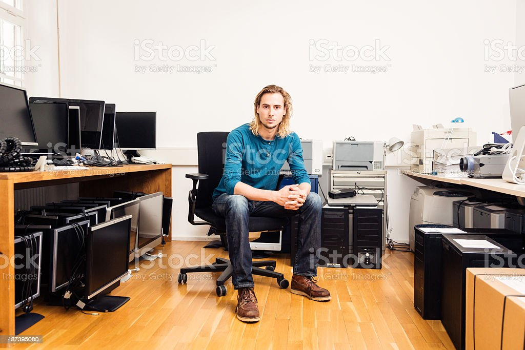system administrator with lots of hardware, computers and monitors stock photo